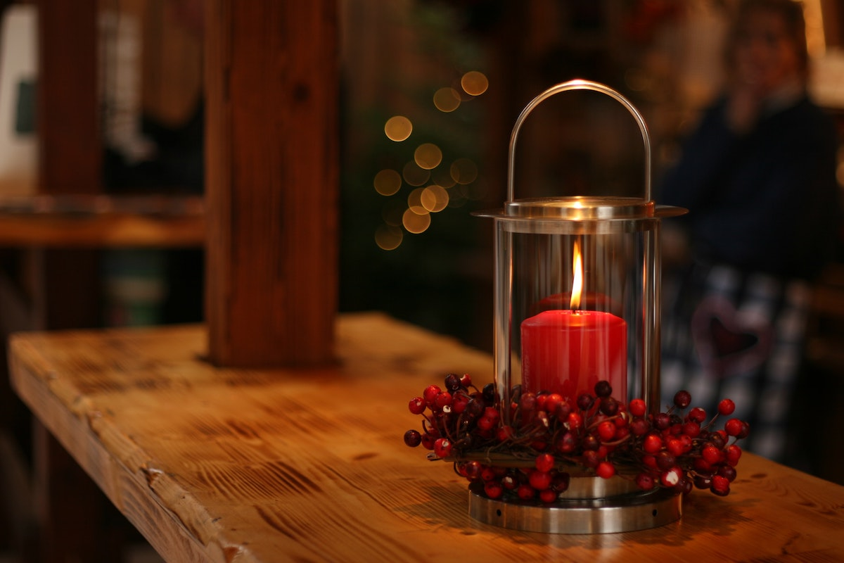 red lighted candal in glass lantern frame with red berry Christmas decoration, placed on a wooden bench