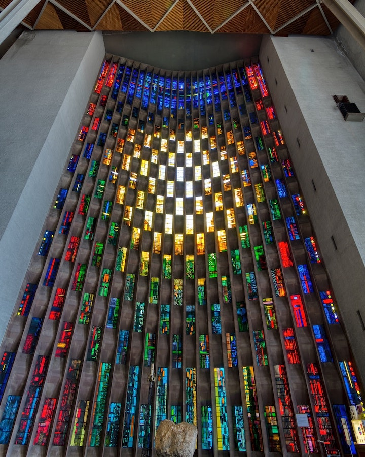 Stained glass window around the font at Coventry Cathedral. The window is broken into small chequered segments of stone and glass, with the glass of different colours. There is a section of light yellows in the centre, reds down the sides, blue at the top, and green underneath the centre.