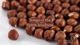 A cluster of shelled hazelnuts on a white surface. Text: Songs of the Spirit: kindness. Faith in Grey Places