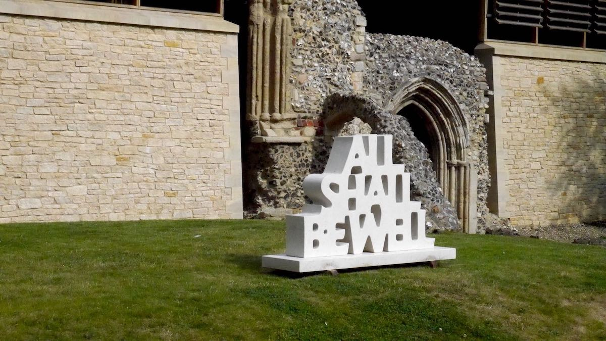 """White stone sculpture outside Norwich Cathedral of the words """"ALL SHALL BE WELL"""""""