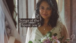 Photo of a bride's face in a mirror. She wears a pearl pendant and looks to the side with a small smile on her face. Words over the top: Songs of the Spirit: joy. Faith in Grey Places