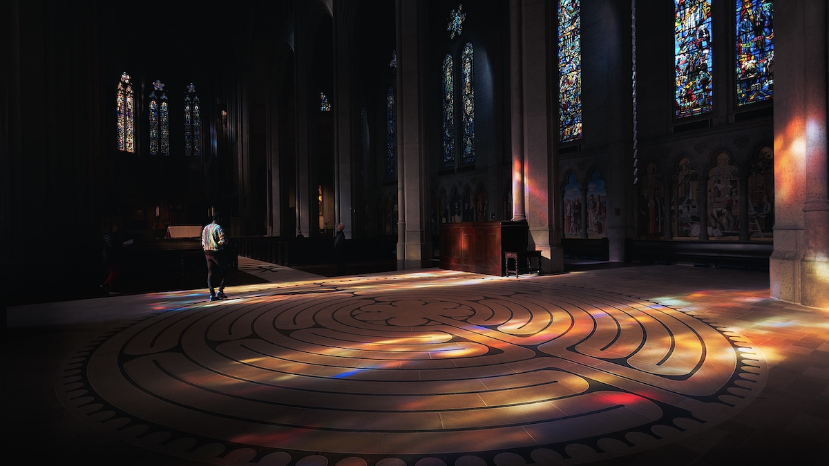 Inside of Chartres Cathedral. The area is dark, but light from stained glass windows behind the camera lights up the stone floor where a labyrinth has been inset into the stone.