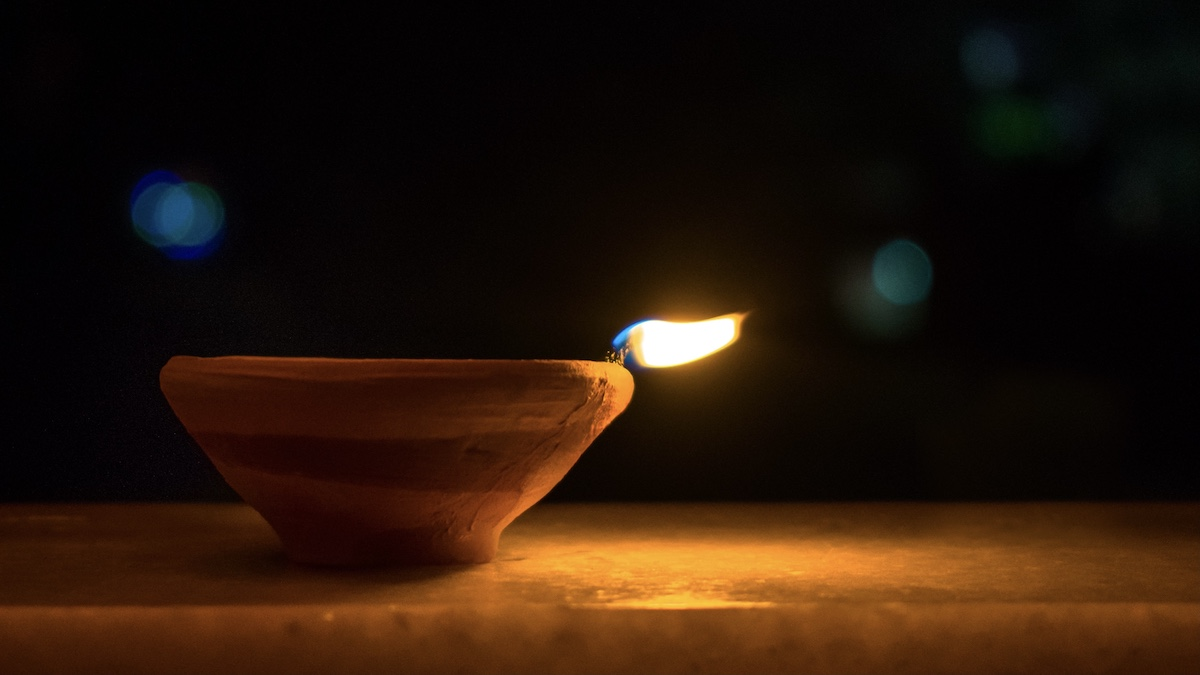 Photo of ceramic oil lamp with a burning wick.