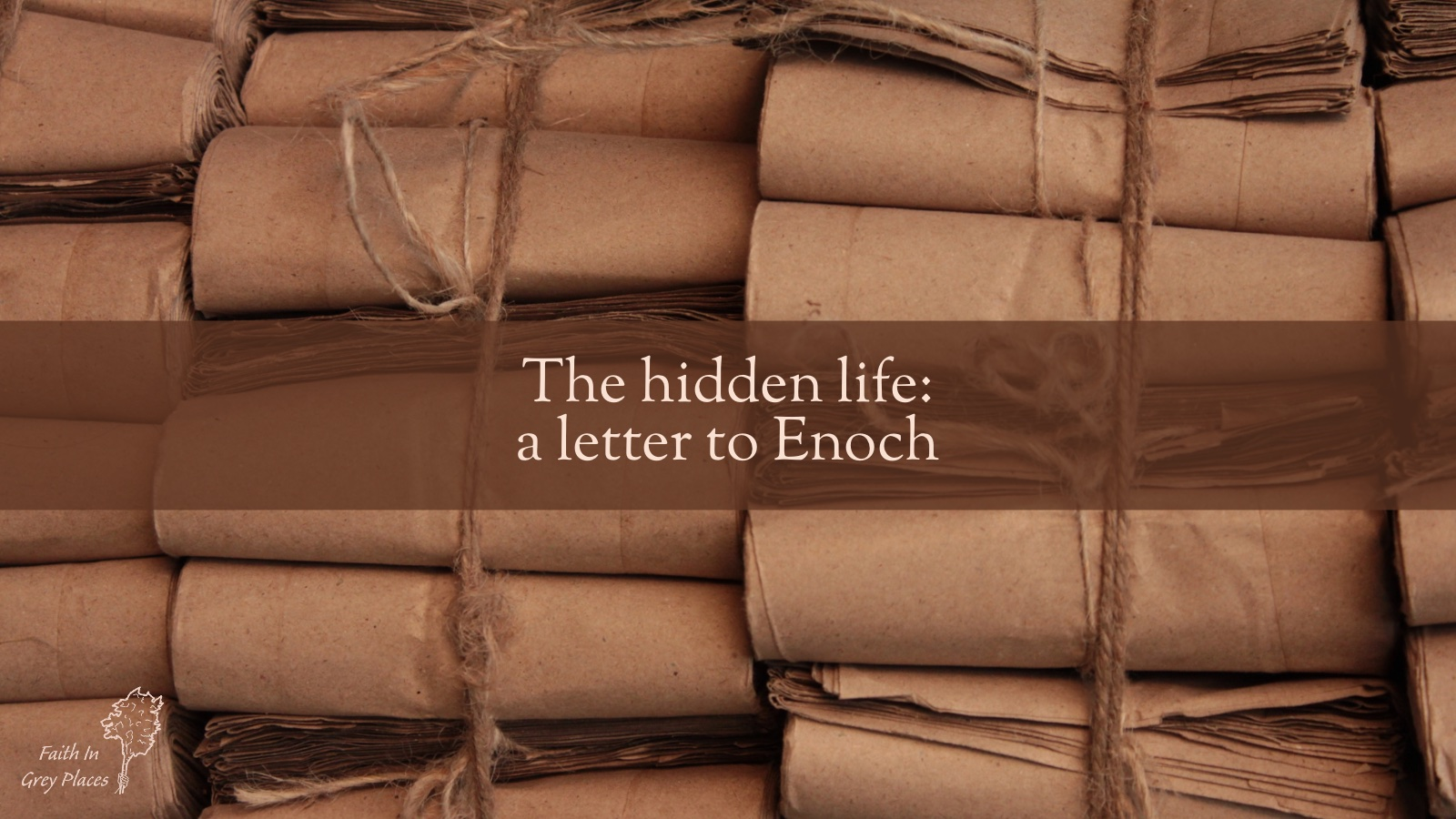 """Rows of brown rolled up paper, tied up with string with words over the top """"The hidden life: a letter to Enoch"""""""